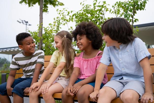 Enfants souriants de plan moyen assis sur un banc