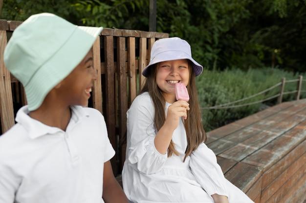 Enfants souriants de plan moyen avec de la crème glacée