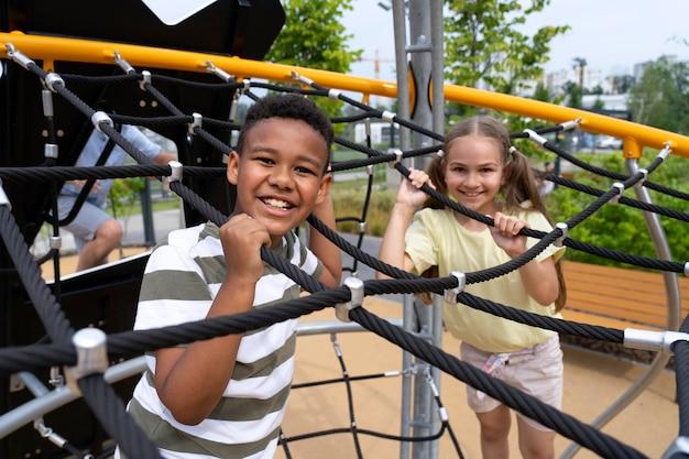 Enfants souriants de plan moyen dans le parc