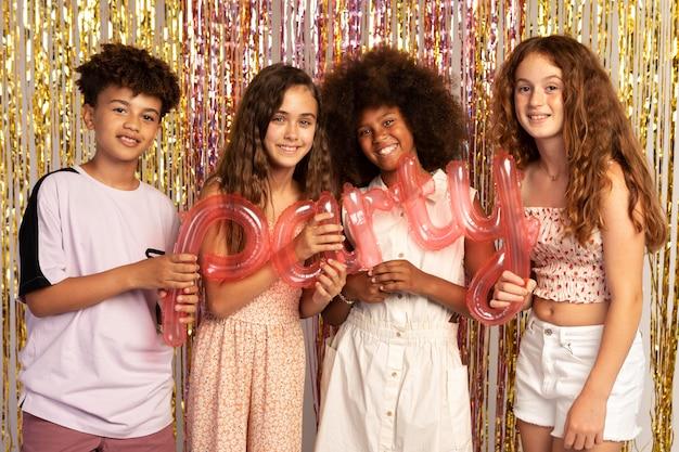 Enfants souriants à plan moyen à la fête