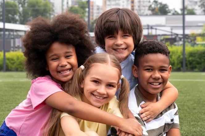 Enfants souriants de plan moyen posant ensemble