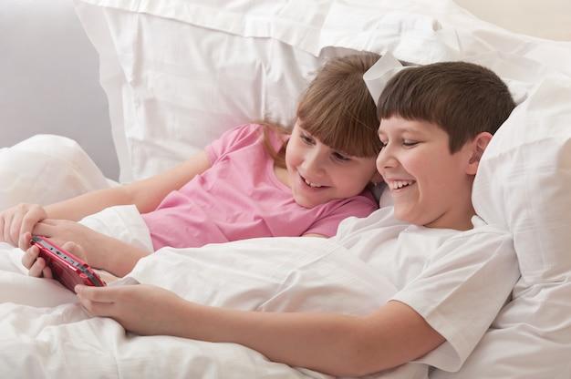 Des enfants souriants sont au lit en train de jouer à une console de jeux. horizontal.