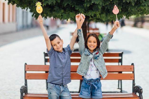 Enfants souriants avec des sucettes, près du banc en bois dans le parc