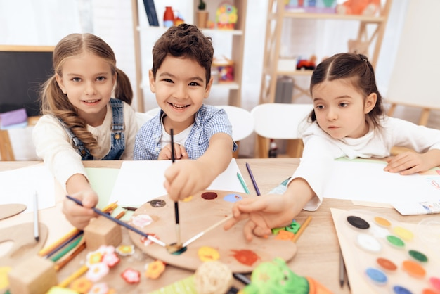 Les enfants suivent un cours de dessin à l'école.