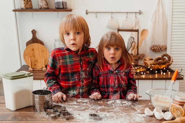 Enfants surpris faisant des biscuits de noël ensemble
