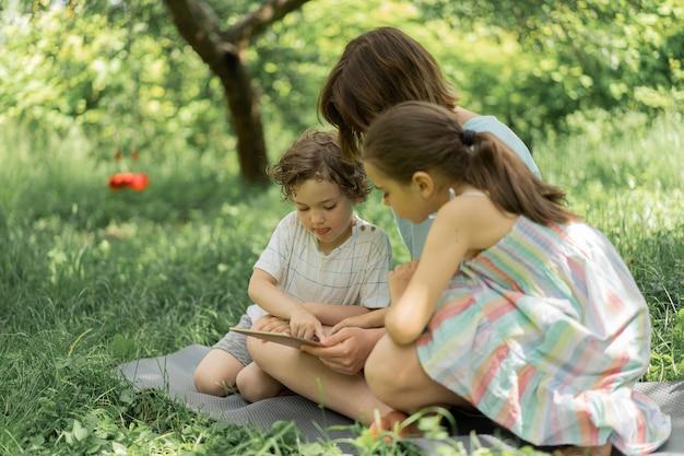 Les enfants avec une tablette à l'extérieur les enfants jouent à des jeux sur le concept de la technologie de la tablette