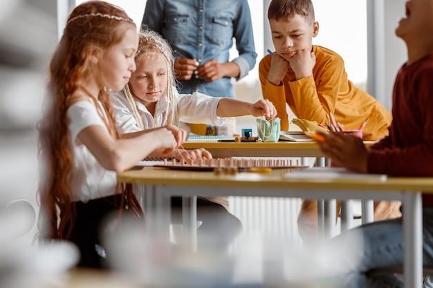 Enfants avec tablette mathématique en bois avec élastiques pour exercices pratiques en maternelle