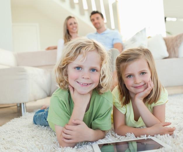 Les enfants sur le tapis avec une tablette et les parents derrière eux