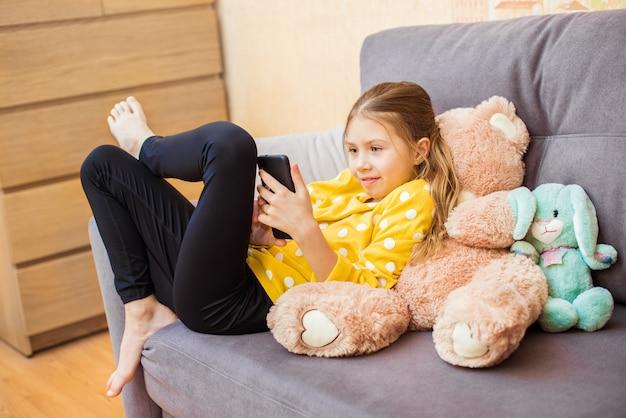 Enfants, Technologie Et Communication Concept Fille Souriante Textos Sur Smartphone à La Maison Photo Premium