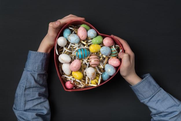 Enfants tenant une boîte en forme de coeur avec des oeufs de pâques colorés. fond noir. cadeau pour pâques.