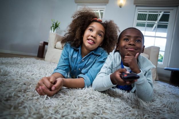 Enfants tenant à distance en position couchée sur le sol