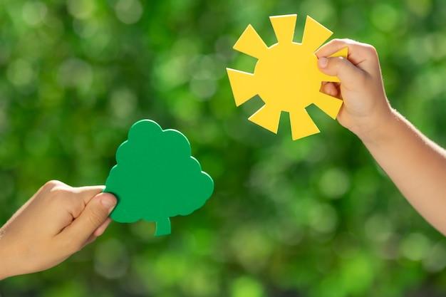Enfants tenant une jeune plante verte dans les mains.