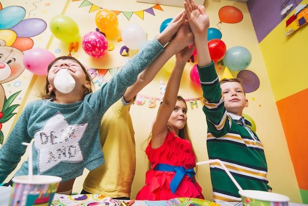 Enfants tenant les mains ensemble sur la fête d'anniversaire