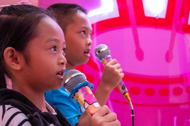 Enfants tenant un micro chantant dans la pièce avec des néons.