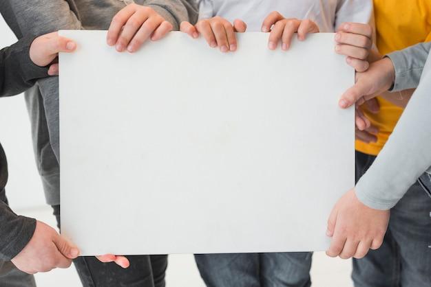 Enfants tenant une pancarte blanche