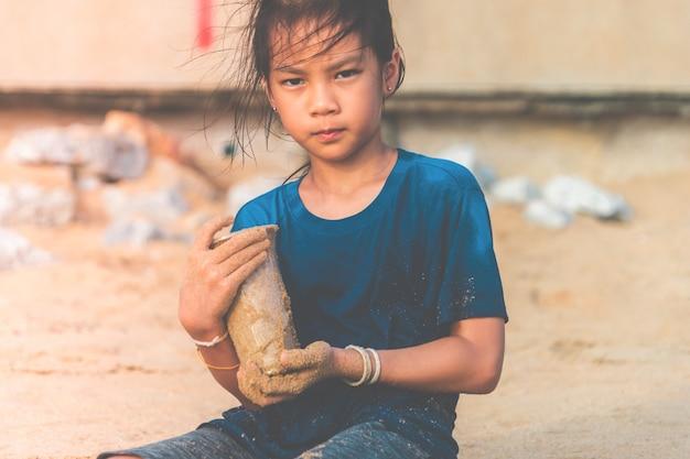 Les enfants tiennent une bouteille en plastique qu'il a trouvée sur la plage
