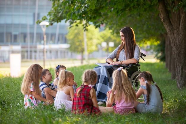 Les enfants tiennent une leçon avec l'enseignant dans le parc sur une pelouse verte.