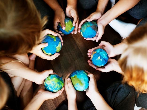 Des enfants tiennent le monde entre leurs mains
