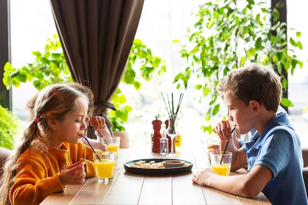 Enfants de tir moyen buvant du jus