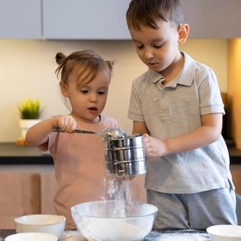 Enfants de tir moyen cuisinant ensemble