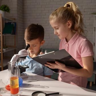 Enfants de tir moyen avec microscope