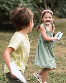 Enfants de tir moyen qui courent à l'extérieur