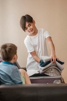 Enfants de tir moyen avec des vêtements pliés