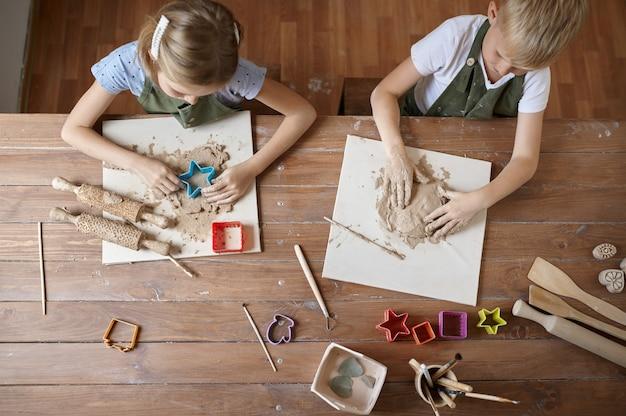 Les enfants travaillent avec de l'argile à table, vue de dessus, enfants en atelier. leçon à l'école des beaux-arts. jeunes maîtres de l'artisanat populaire, passe-temps agréable, enfance heureuse
