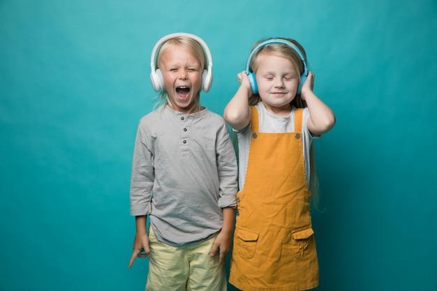 Des enfants très émotifs écoutent de la musique avec des écouteurs sur fond bleu.