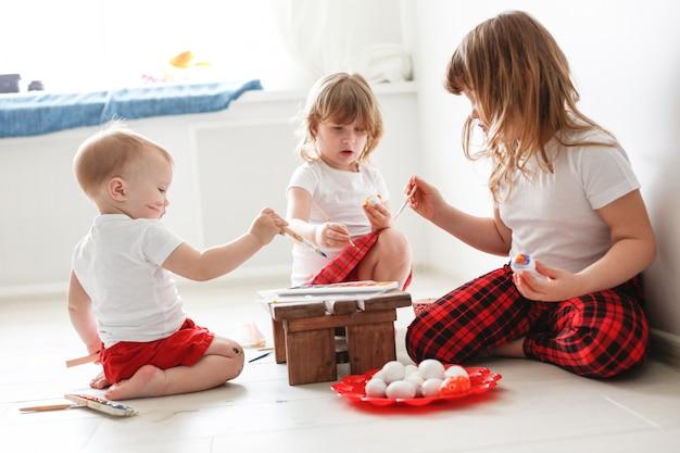 Enfants trois frères et sœurs peignent des œufs, pâques