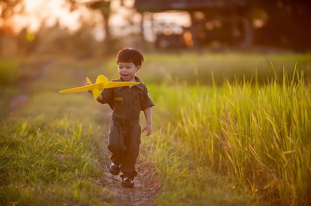 Les enfants en uniforme de l'armée de l'air jouent des avions dans les champs avant le coucher du soleil