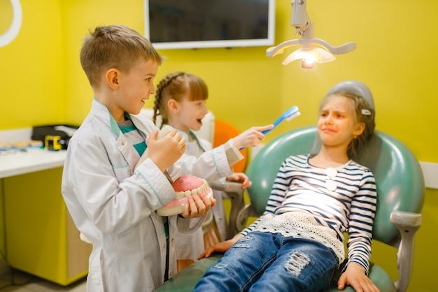 Enfants en uniforme jouant au médecin dentiste