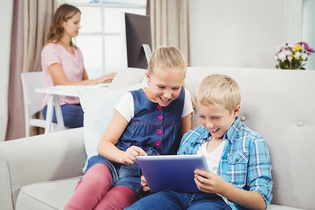 Enfants utilisant une tablette numérique alors que la mère est à l'arrière-plan