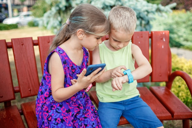 Les enfants utilisent des montres intelligentes avec attention et les parents contrôlent les nouvelles technologies pour les enfants