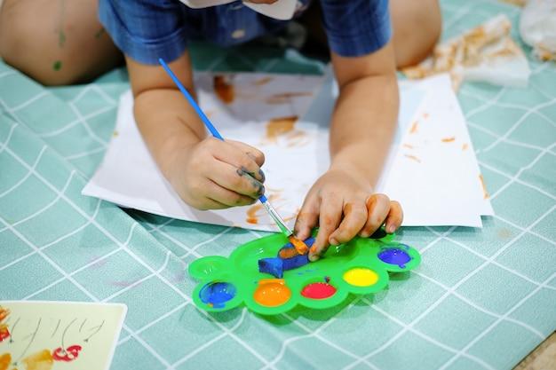 Les enfants utilisent des pinceaux aquarelle pour créer de l'imagination et améliorer leurs compétences d'apprentissage.
