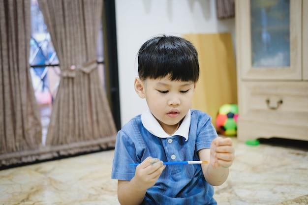 Les enfants utilisent des pinceaux à l'aquarelle pour dessiner sur leurs bras afin de créer de l'imagination et d'améliorer leurs capacités d'apprentissage.