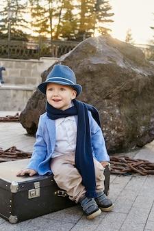 Les enfants avec des valises voyagent, des vêtements de printemps automne rétro.