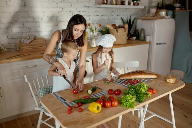 Les enfants végétaliens apprennent à préparer une salade dans la cuisine. journée de repos en famille, déjeuner de vos propres mains. maman et jeunes cuisiniers végétaliens