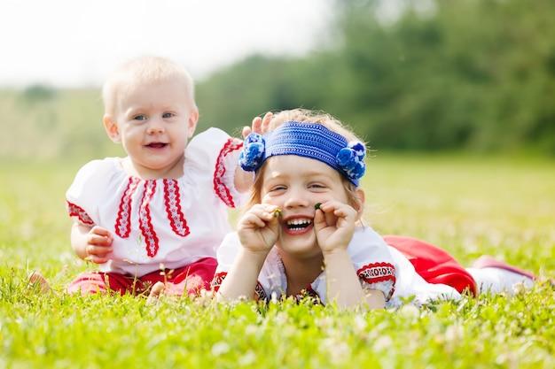 Enfants en vêtements folkloriques sur l'herbe