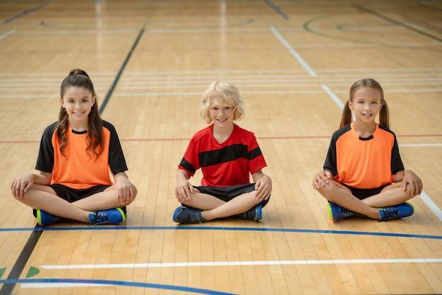 Enfants vêtus de vêtements de sport lumineux assis en posture de lotus