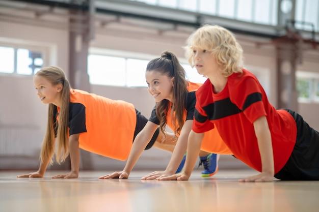 Enfants vêtus de vêtements de sport lumineux faisant des pompes