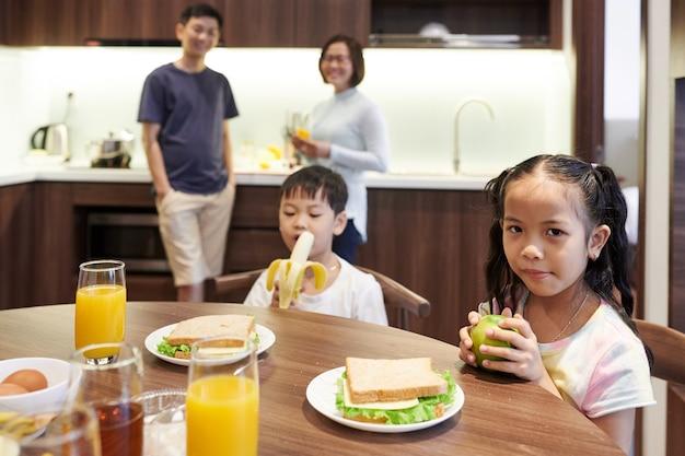 Enfants vietnamiens préadolescents assis à la table de la cuisine et mangeant des sandwichs et des fruits pour le petit-déjeuner