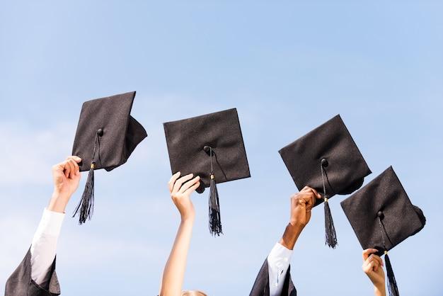 Enfin diplômé! close-up de quatre mains tenant des planches de mortier sur fond de ciel