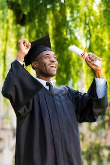 Enfin diplômé! heureux jeune homme africain en robes de graduation tenant un diplôme et levant les bras