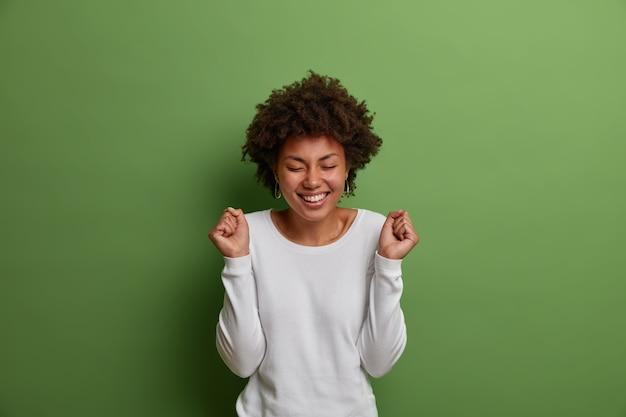 Enfin je l'ai gagné! une femme joyeuse qui réussit lève les mains avec enthousiasme, serre les poings en triomphe, applaudit avec un sourire radieux et les yeux fermés, se réjouit du prix gagnant, se tient à l'intérieur sur un mur végétal