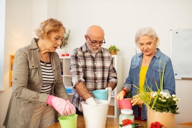 Engagé dans le jardinage. personnes âgées sérieuses regardant dans les pots de fleurs tout en étant engagées dans le jardinage