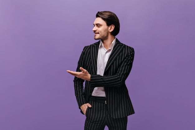 Engager un jeune garçon aux cheveux bruns en chemise légère et costume rayé classique pointant de côté sur l'espace de copie avec une main isolée sur un mur violet