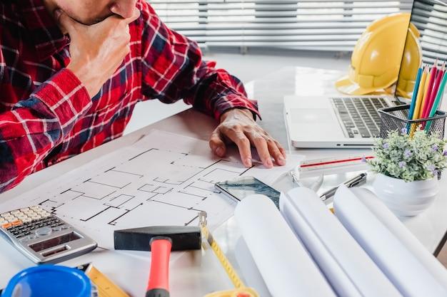 Engineman rman main travaillant avec le nouvel ordinateur portable moderne et blueprint avec materi