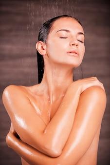 Enlever le stress. belle jeune femme torse nu debout dans la douche et se laver les cheveux