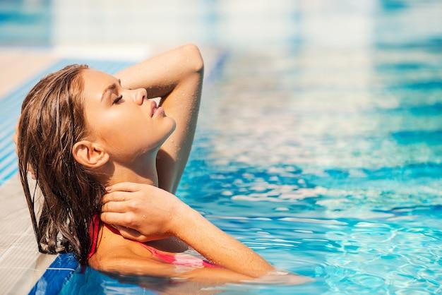 Enlever le stress. vue latérale d'une belle jeune femme en bikini ajustant ses cheveux mouillés et gardant les yeux fermés en se tenant debout à la piscine